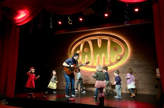 Camp theater with musician and children playing music