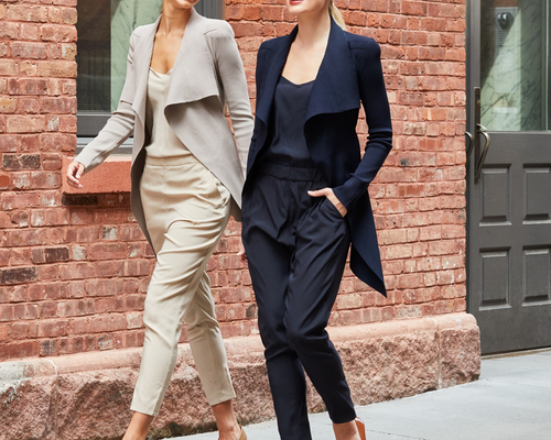 two women walking in silk pants and jackets one beige and one black