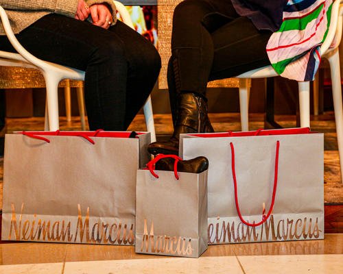 two woman sitting with Neiman Marcus silver shopping bags