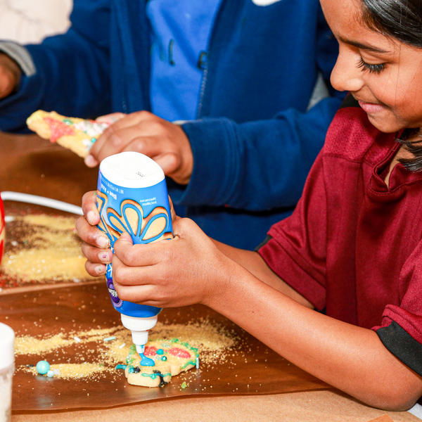 children decorating cookies with icing