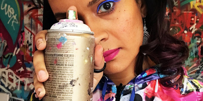 Artist Indie184 holding a spray can